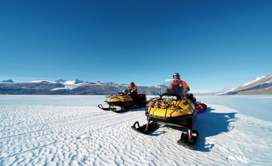 Das Reisen in der Antarktis ist während des Sommers relativ einfach. Hier fahren zwei Wissenschaftler auf Skidoos zu ihrem Forschungslager auf dem Taylor Gletscher, aber Bedingungen im Winter werden neue Herausforderungen für die Forscher bringen. (Foto: Katja Riedel)